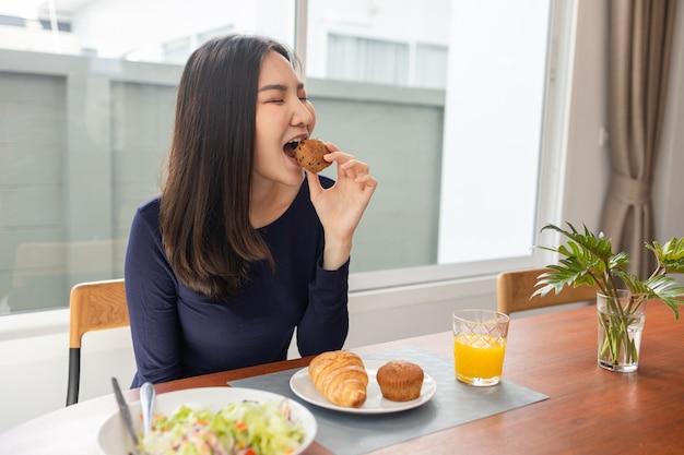 Tendo o conceito de refeição, uma jovem comendo um bolinho como sobremesa com suco de laranja, depois de comer salada na casa dela.