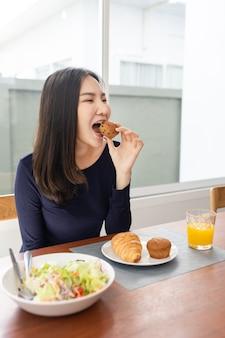 Tendo o conceito de refeição uma jovem comendo um bolinho como sobremesa com suco de laranja, depois de comer salada na casa dela.