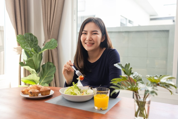 Tendo o conceito de refeição uma mulher bonita misturando molho de salada de zero calorias com uma salada verde