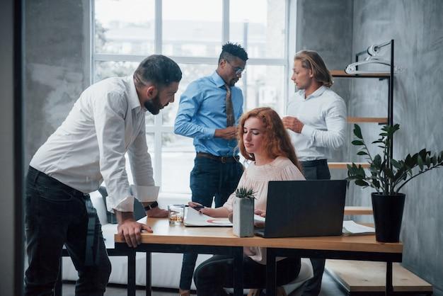 Tendo problemas para resolver. equipe de negócios jovem trabalhando em um projeto com o laptop na mesa na frente deles