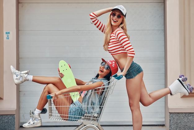 Tendo um dia louco juntos. vista lateral de uma jovem feliz de patins carregando sua amiga no carrinho de compras e sorrindo enquanto patinava contra a porta da garagem