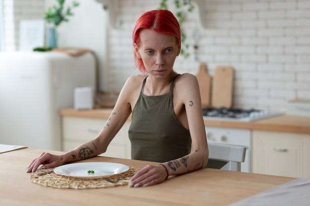 Tendo uma aparência horrível. mulher anoréxica tatuada com uma aparência horrível sentada na cozinha perto de um prato com três ervilhas