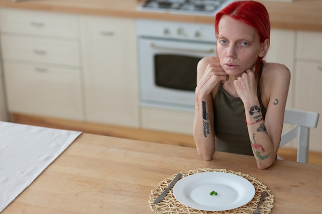Tendo uma aparência insalubre. mulher ruiva tatuada, anorexia e aparência doentia