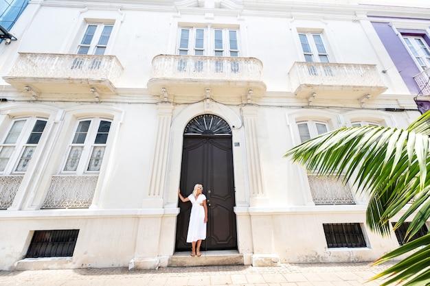 Tenerife, ilhas canárias, espanha. uma garota em um vestido branco está encostada na parede de uma casa em santa cruz de tenerife.