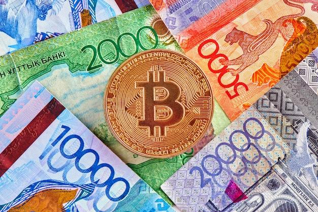 Tenge cazaque dinheiro e criptomoeda bitcoin close-up. conceito de investimento em moeda virtual digital na internet