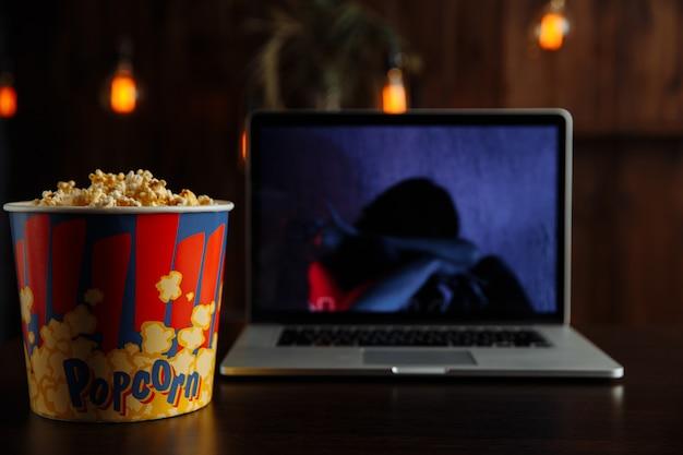 Tenha uma boa noite assistindo a um filme em um laptop com pipoca.