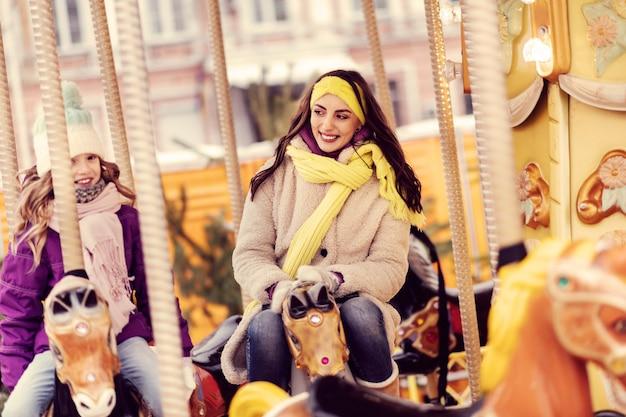 Tenha uma ideia. mulher encantada expressando positividade sentada em um cavalo artificial