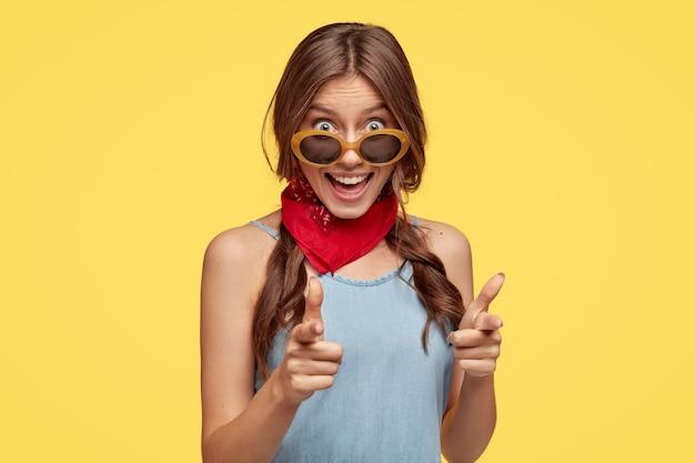 Tenho bons planos para você. alegre garota na moda aponta com os dois dedos indicadores diretamente para algo maravilhoso, usa óculos de sol da moda, isolados sobre a parede amarela.