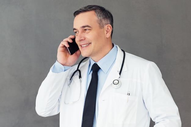 Tenho ótimas notícias para você! médico homem maduro falando no celular com um sorriso em pé contra um fundo cinza