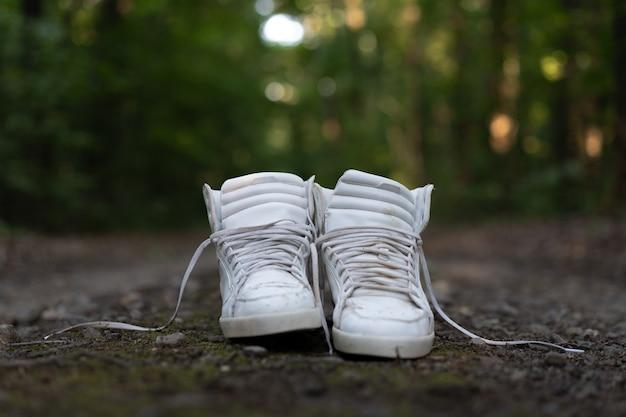 Tênis altos brancos ficam em uma estrada rural que corre na floresta.