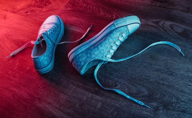 Tênis antiquados em piso de madeira com brilho gradiente de néon vermelho-azul