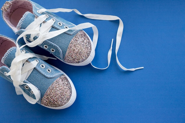 Tênis azuis na moda para meninas isoladas na parede azul. par de sapatos de desporto para crianças na moda.tênis de brim da moda para crianças.par de tênis brilhantes na moda, com atacadores brancos. estilo da juventude