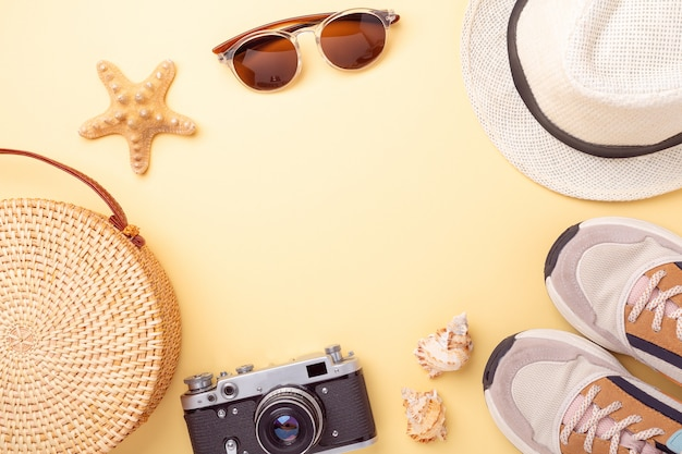 Tênis, bolsa de vime, óculos escuros, chapéu e câmera retro em um fundo amarelo. conceito de viagens. configuração plana