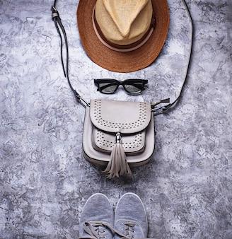 Tênis, bolsa, óculos escuros e chapéu.
