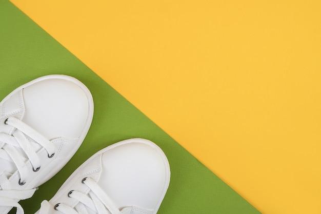 Tênis branco com cadarço no chão verde e amarelo