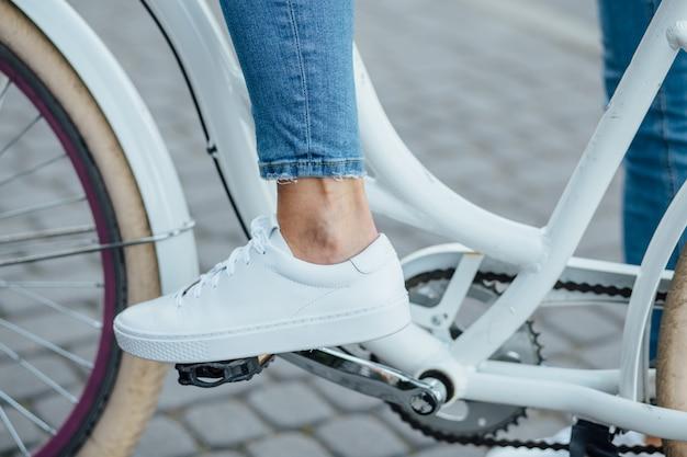Tênis branco e calça jeans azul em um pedal de bicicleta