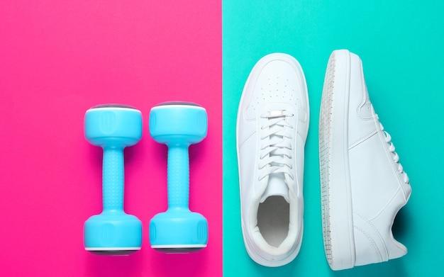 Tênis branco, halteres de plástico em um fundo de duas cores. conceito de esporte. vista do topo