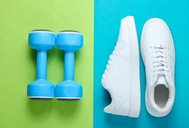 Tênis branco, halteres de plástico sobre uma mesa de duas cores. conceito de esporte. vista do topo