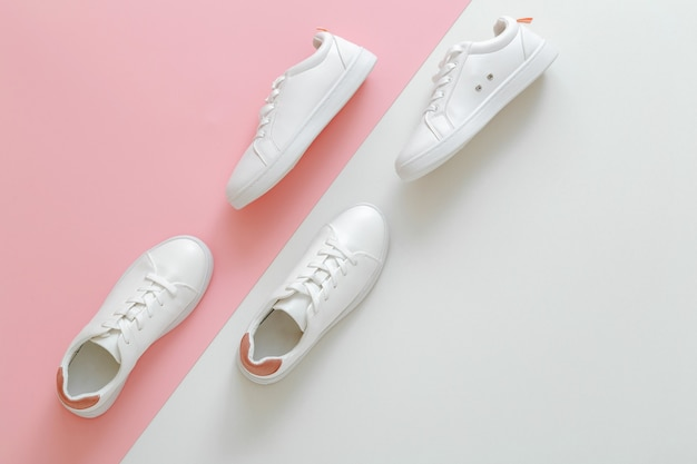 Tênis branco masculino e feminino na cor de fundo rosa. sapatos de couro branco com atacadores com espaço de cópia. dois pares de tênis elegantes. confortáveis roupas esportivas e sapatos femininos modernos.