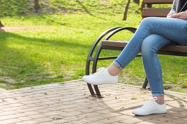 Tênis branco nas pernas femininas em jeans azul no asfalto e fundo de grama verde.