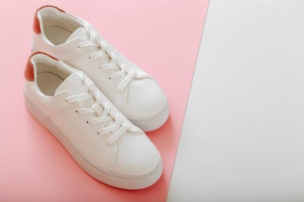 Tênis branco sobre fundo cor-de-rosa. sapatos femininos de couro branco com atacadores em fundo rosa com espaço de cópia. par de tênis elegantes. calçados femininos, modernos, esportivos e confortáveis.