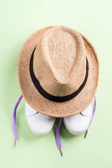Tênis brancos com laços roxos e chapéu de palha