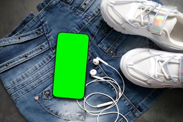 Tênis brancos modernos e elegantes, telefone inteligente com chromakey de tela verde e fones de ouvido. roupa urbana para a vida diária, boa forma e estilo de vida ativo e saudável ou viagens de férias.