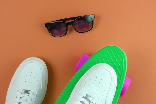 Tênis brancos na mini placa cruiser de plástico e óculos de sol. fundo marrom. diversão de verão. vista do topo