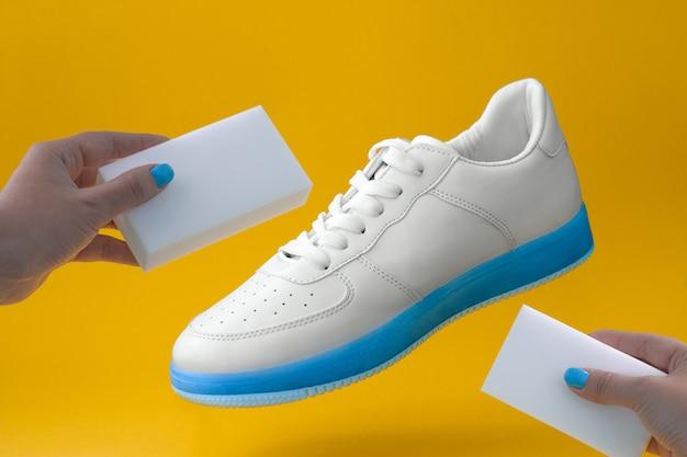 Tênis brancos na moda com sola azul e mãos femininas com esponjas em um fundo amarelo