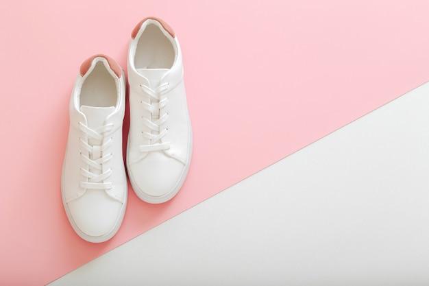 Tênis brancos, sapatos femininos de couro branco com atacadores no fundo rosa. par de tênis elegantes. calçados femininos, modernos, esportivos e confortáveis. espaço da cópia da vista superior.