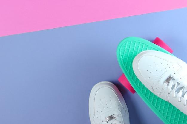 Tênis brancos sobre placa de mini cruiser de plástico. fundo de cor pastel. vista do topo