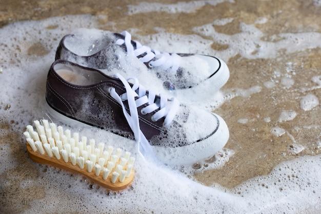 Tênis com espuma de dissolução de água em pó detergente e escova de madeira no chão de cimento. lavando sapatos sujos.