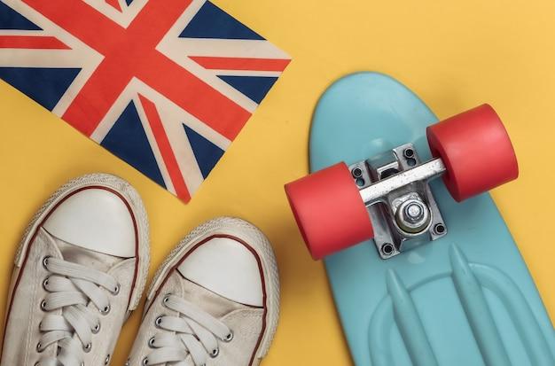 Tênis da velha escola, cruiser board e bandeira britânica em um amarelo