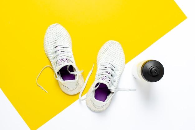 Tênis de corrida brancos e uma garrafa de água em um fundo amarelo-branco abstrato. conceito de corrida, treinamento, esporte.