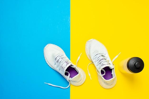 Tênis de corrida brancos e uma garrafa de água em uma superfície amarela e azul abstrata. conceito de corrida, treinamento, esporte. . vista plana, vista superior