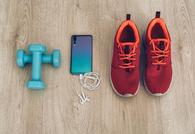 Tênis de corrida com smartphone, fones de ouvido e halteres