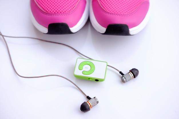 Tênis de corrida rosa para mulheres e mp3 player com fones de ouvido em um fundo branco