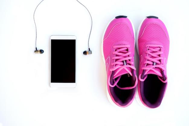 Tênis de corrida rosa para mulheres, telefone e fones de ouvido em um fundo branco