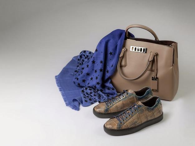 Tênis de couro de crocodilo ao lado de uma bolsa de couro e um cachecol de lã