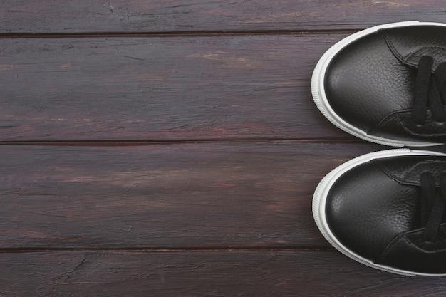 Tênis de couro preto casual em fundo de madeira