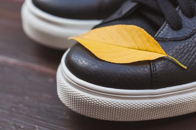 Tênis de couro preto com folha amarela sobre fundo de madeira. conceito de outono