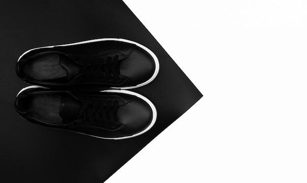 Tênis de couro preto sobre fundo preto e branco