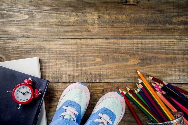 Tênis de crianças, livros, lápis de cor e despertador no fundo da mesa de madeira