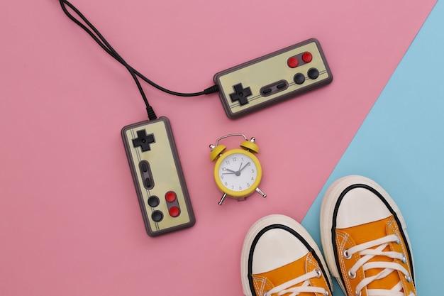 Tênis de juventude retrô, videocassete e mini despertador em fundo rosa azul pastel. anos 80.