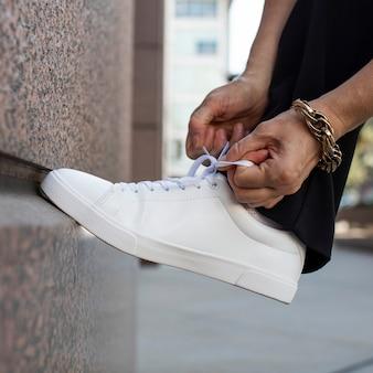 Tênis de lona branco modelo amarrando cadarços anúncio de roupas