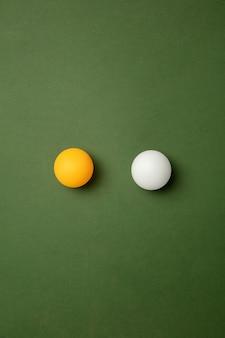 Tênis de mesa brilhante, bolas de pingue-pongue. equipamento de esporte profissional isolado sobre fundo verde.