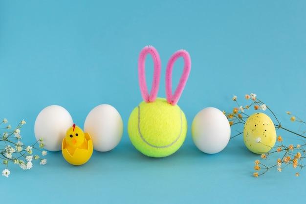 Tênis de páscoa com uma bola de tênis sorridente com orelhas de coelho, ovos de galinha branca e gipsófila sobre fundo azul.
