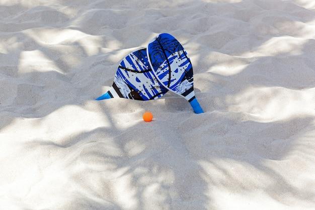 Tênis de praia, na sombra das palmas há raquetes e uma bola na areia, set para pingue-pongue