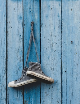 Tênis de têxteis muito antigo pendurado em um prego
