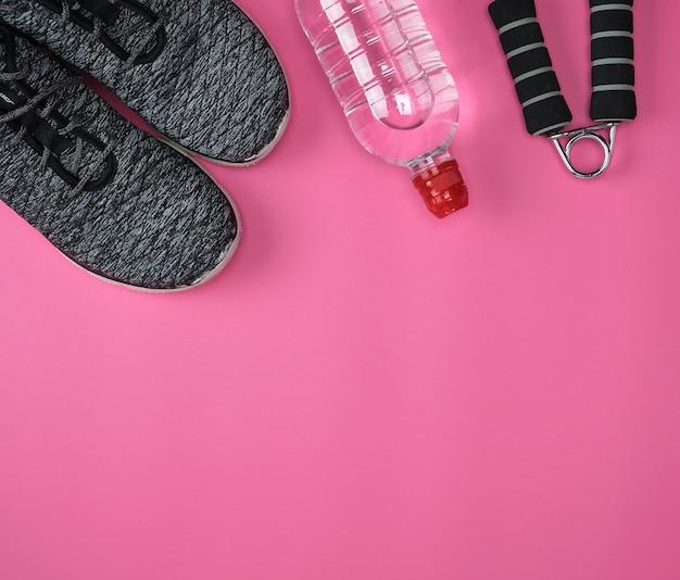 Tênis de têxtil preto, uma garrafa de água em um fundo rosa